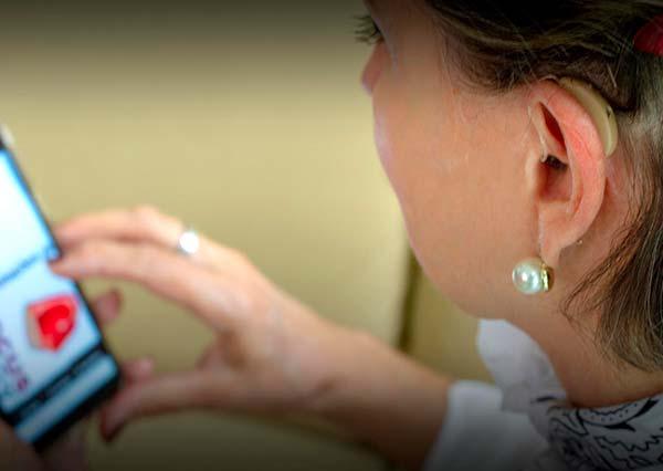 Mulher usando aparelho auditivo